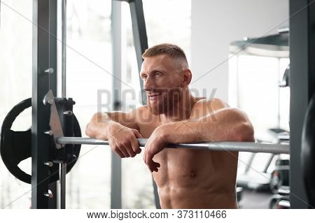 Gym Man Leaning Barbell Resting After Hard Training. Handsome Caucasian Athlete Take Break. Sport Eq