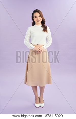 Businesswoman Standing With Folded Hands. Smilng Woman On Purple Wall Background.