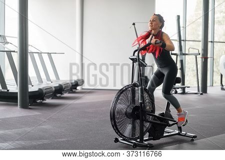 Woman Exercise Bike Gym Cycling Training Fitness. Fitness Female Using Air Bike Cardio Workout. Athl