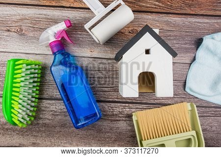 Wooden Model White Houses And House Cleaning Equipment On A Teble Wooden  Background. Concept Clean