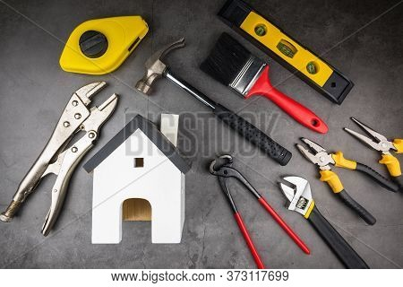 Wooden Model White Houses And Home Repair Hand Tools On A Cement Gray Background. Concept Home Repai