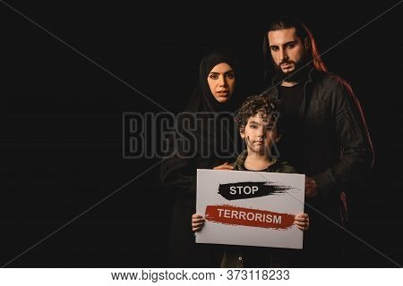 Kid Holding Card With Stop Terrorism Lettering Near Parents Isolated On Black
