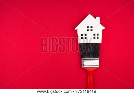 Wooden White House And Paint Brushes On Red Background With Copy Space.real Estate Concept, New Hous