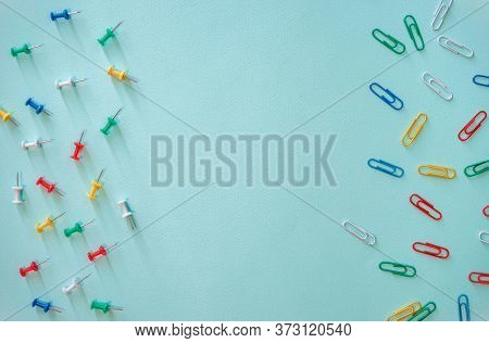 Multi-colored Paper Clips And Stationery Buttons Arranged Randomly. Paper Clips In The Right Part Of