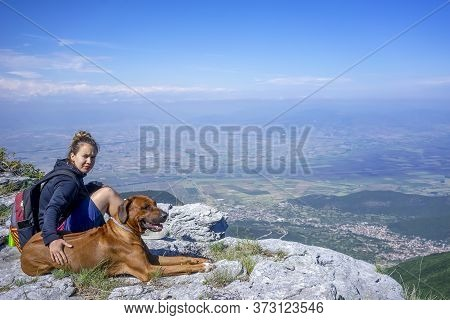 Girl With A Rhodesian Ridgeback Dog In The Mountains