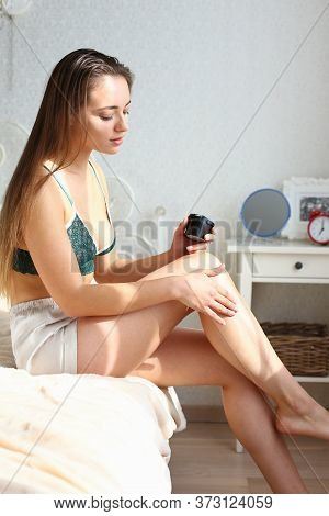 Attractive Lady With Long Hair Sitting On Bed And Touching Her Leg With Soft Silky Skin