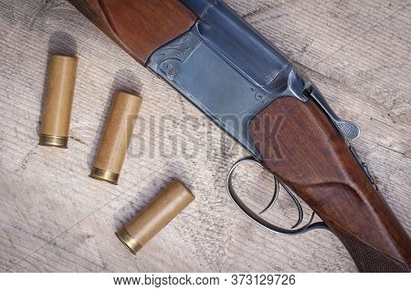 Shotgun Forearm With Two Triggers Top View. Rifle Charges Or Cartridges On A Wooden Surface. Hunting