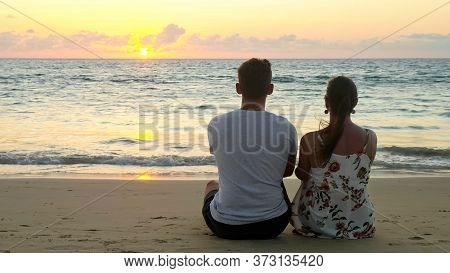 Lovely Young Couple Sits On Empty Ocean Beach Watching Sunset At Tropical Resort In Evening Backside