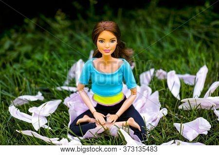 Tambov, Russian Federation - June 12, 2020 Brunette Barbie Doll Sitting In The Yoga Lotus Posture Ou