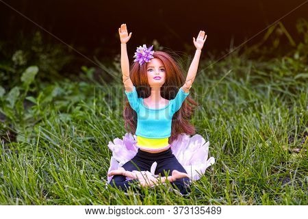 Tambov, Russian Federation - June 12, 2020 Brunette Barbie Doll Doing Yoga In The Lotus Posture Outd