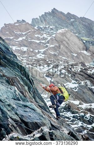 Side View Alpinist With Backpack Using Fixed Rope To Climb High Rocky Mountain. Man Climber Ascendin