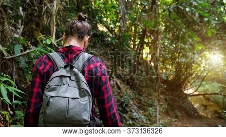 Woman With Hair Bun Wearing Checkered Shirt And Backpack Enjoys Hiking And Walks In Lush Tropical Fo
