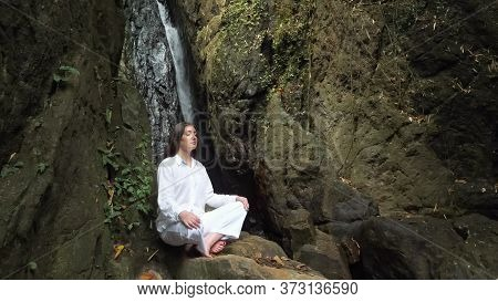 Concentrated Young Woman With Loose Dark Hair In Special White Costume Sits With Closed Eyes In Yoga
