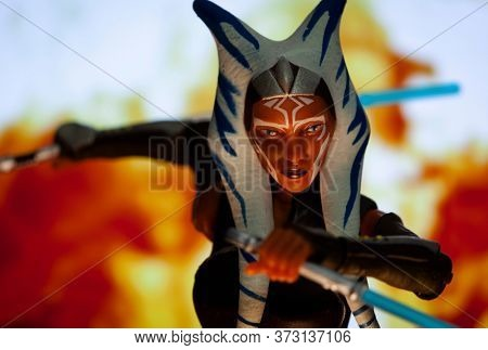 JUNE 21 2020: Recreation of a scene from Star Wars The Clone Wars with Jedi Ahsoka Tano posed for action with her light sabers - Hasbro action figure