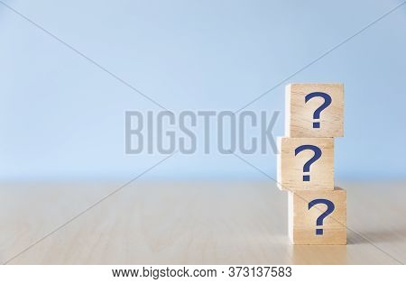Questions Mark ( ? ) Word With Wooden Cube Block On Table Background. Frequency Asked Questions, Ans