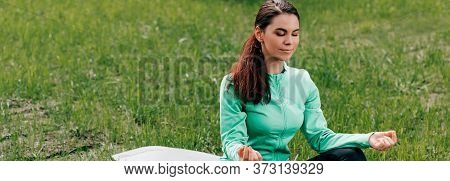 Crop Of Young Woman Meditating On Fitness Mat In Park