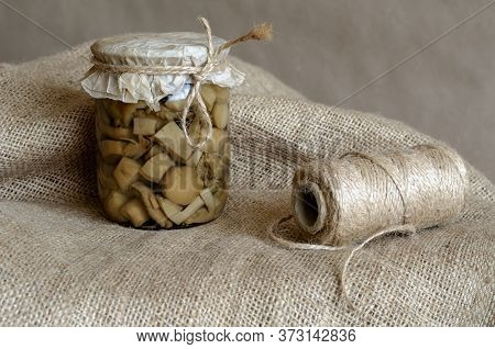Glass Jar With Canned Wild Mushrooms On Burlap. Glass Bowl With Mushrooms And Twine Close-up. Long-t