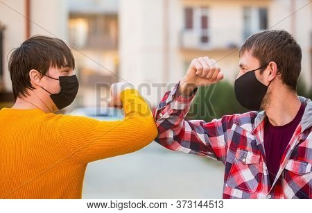 Friends In Protective Medical Mask On His Face Greet Their Elbows In A Quarantine. Elbow Bump. Frien