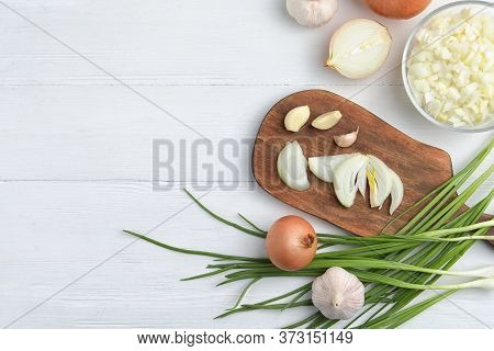 Flat Lay Composition With Cut Onion And Garlic On White Wooden Table. Space For Text