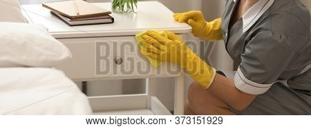 Young Chambermaid Wiping Dust From Nightstand In Bedroom, Closeup. Banner Design