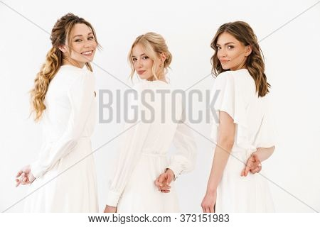 Photo from back of happy charming three women with fingers crossed for good luck isolated over white wall