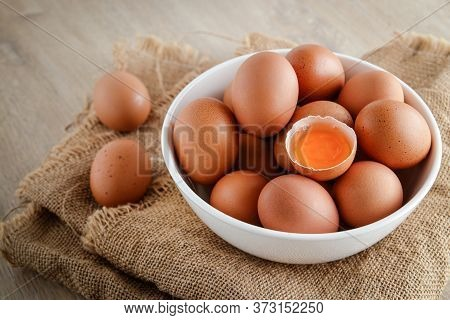 Many Organic Chicken Eggs Are Placed In A White Bowl. And With An Egg Yolk Placed In The Middle Is A