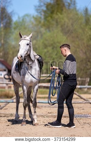Young Man Works On A Cord With Horse At The Manege At Summer