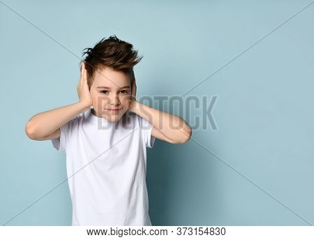 Sly Naughty Kid Smiling And Covering Ears With Hands Showing He Does Not Want To Hear And Obey. Faci