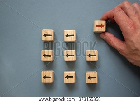 Individuality Conceptual Image. Male Hand With Wooden Cubes On Beautiful Blue Background.