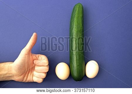 Male Hand Holds Thumb Up A Cucumber With Eggs. Sexual Organ Concept