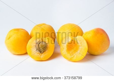 Apricots On A White Background. Front Two Slices Of Apricot. One Lobule With A Bone, The Other Witho