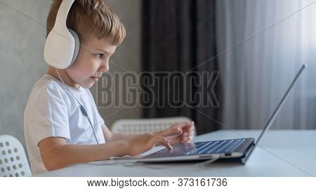 Cute Diligent Boy Is Typing On The Keyboard And Is Carefully Looking At The Laptop Screen. Caucasian