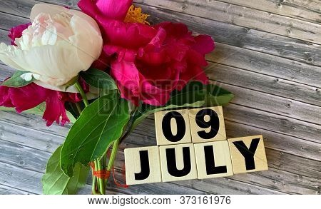 July 9. July 9 On Wooden Cubes On A Wooden Background.peonies.photos For The Holiday .