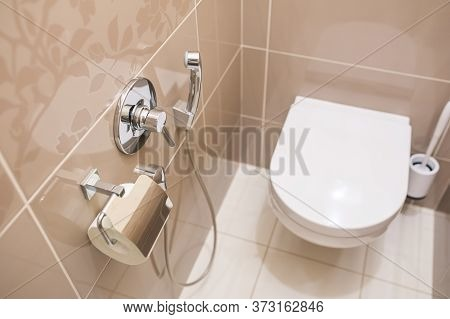 Hygienic Shower With Faucet And Toilet Paper On The Tiled Wall In The Toilet. Hanging White Toilet A
