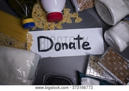 Donate Sign Handwritten With Black Letters. A Pile Of Food Supplies On A Grey Table. Food Donation C