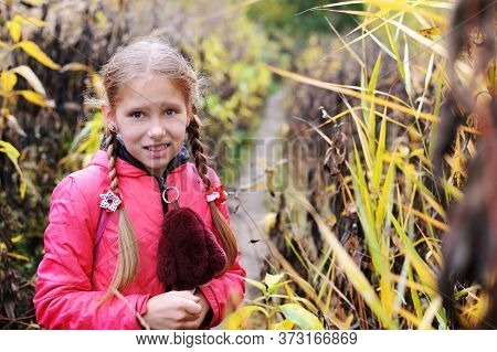 The Young Girl With A Frightened Face Stands Among The Abandoned Garden. She Thinks She's Lost