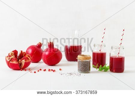 Pitcher And Two Jars Of Fresh Pomegranate Juice, With Three Ripe Pomegranates, One Freshly Peeled. R