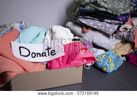 Donate Sign Handwritten With Black Letters. A Box With Clothes And A Pile Of Clothes Nearby On A Gre