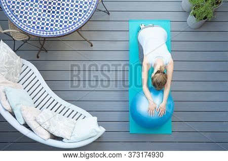 Overhead View Of Healthy Mature Woman At Home Exercising On Deck  With Swiss Exercise Ball