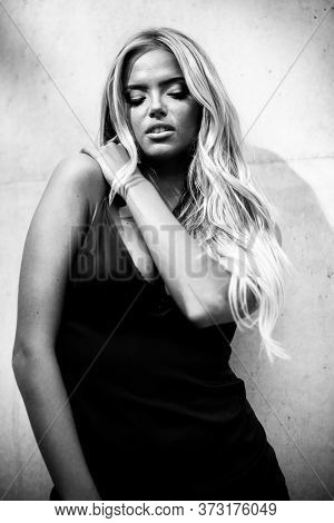 Blond young woman with beautiful makeup and hair in black dress standing near grey wall. Fashion model posing in elegant clothes outdoors in urban enviroment. Black and white, monochrome.