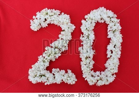 The Number 20 Is Written In White Lilac Flowers On A Red Background. The Number Twenty Is Written In