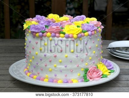 Pastel Rainbow Yellow, Pink, Purple Butter Cream Frosting Handmade Roses On A Round Cake Frosted Wit