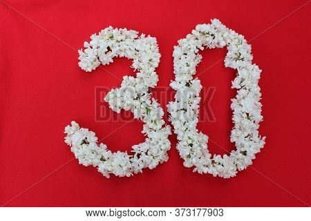 The Number 30 Is Written In White Lilac Flowers On A Red Background. The Number Thirty Is Written In