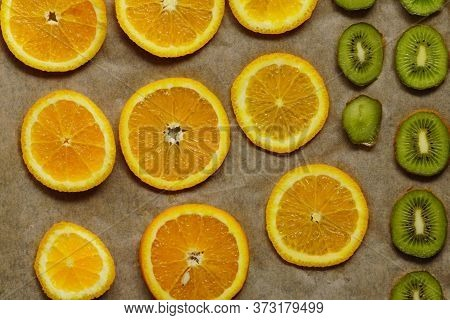 Orange And Kiwi Cut Into Circles And Lie On Baking Sheet On Baking Paper. Homemade Dried Fruit In Th