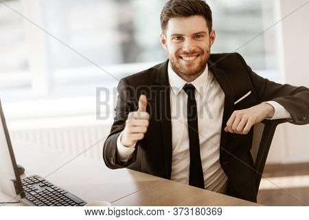 Business concept. Successful young businessman at work. Manager sitting at the office table happy showing thumb up. Man smiling in suit indoors on glass window background.