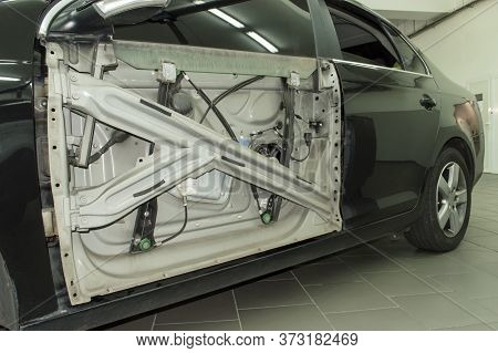 A Dark Gray Car Is Parked In An Auto Repair Shop With The Front Panel Of The Front Door Removed, A V