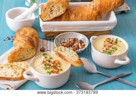 Blue Wooden Table With 2 Bowls Of Cauliflower Soup Embellished With Crushed Hazelnuts, Red Pepper, S