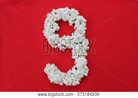The Number 9 Is Written In White Lilac Flowers On A Red Background. The Number Nine Is Written In Fr
