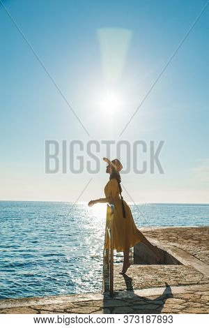 Young Pretty Woman In Yellow Sundress At Sea Beach