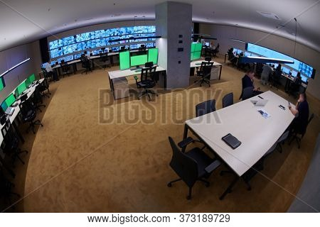 Group of Security data center operators working in a CCTV monitoring room looking on multiple monitors  Officers Monitoring Multiple Screens for Suspicious Activities  Team working on he System Contro
